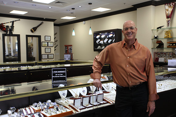 Chip Hurd standing in front of a pre-owned luxury watch display case