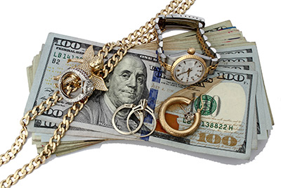 Stack of cash with gold watches and jewelry resting on top
