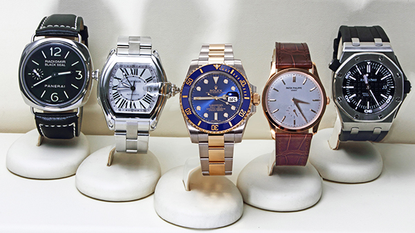 Pre-owned luxury rolex, panerai, cartier, patk philippe watches displayed on watch stands